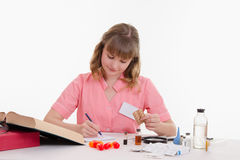 Pharmacist rewrites name tablets to notebook Stock Photography
