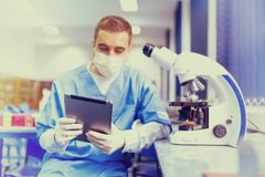 Pharmacist and scientist looking at tablet and comparing microscope results Royalty Free Stock Image