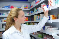 Pharmacist searching. The right medicine at the pharmacy royalty free stock photo