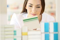 Pharmacist searching medicines in a pharmacy. Front view of a pharmacist searching medicines in a pharmacy interior stock photography