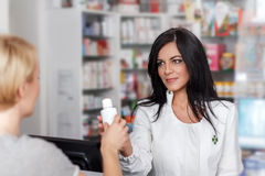 Pharmacist selling medicine in drugstore Royalty Free Stock Photos