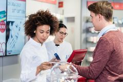 Pharmacist selling prescribed medicines to a customer in a moder Royalty Free Stock Image