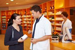Pharmacist selling to customer. Pharmacist giving advice and selling to female customer in pharmacy Stock Photos