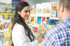 Pharmacist selling a toy to a client Stock Image