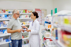 Pharmacist and senior man buying drug at pharmacy. Medicine, pharmaceutics, health care and people concept - happy pharmacist giving drug to senior men customer Stock Photos
