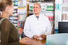 Pharmacist serving client in pharmacy Stock Photo