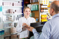 Pharmacist serving client in pharmacy Royalty Free Stock Photo
