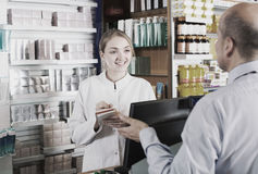 Pharmacist serving client in pharmacy Royalty Free Stock Images
