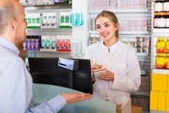 Pharmacist serving client in pharmacy Stock Image