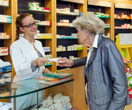 Pharmacist serving a senior lady Stock Images