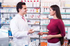 Pharmacist serving woman in pharmacy Stock Image
