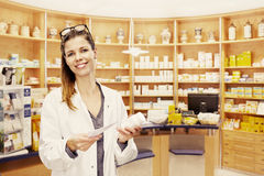 Pharmacist shelf pharmacy. Pharmacist with glasses on her head in front of shelf with medication in pharmacy Royalty Free Stock Photo
