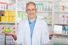 Pharmacist showing apple and medicin. In his hands Royalty Free Stock Photos