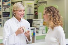 Pharmacist showing blister packs to costumer Stock Photos