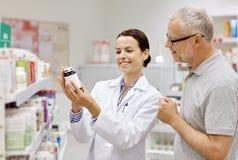 Pharmacist showing drug to senior man at pharmacy Royalty Free Stock Photos