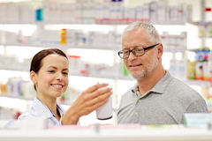 Pharmacist showing drug to senior man at pharmacy Royalty Free Stock Image