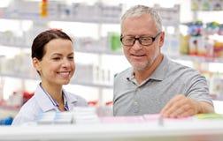 Pharmacist showing drug to senior man at pharmacy Royalty Free Stock Photography
