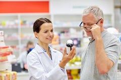 Pharmacist showing drug to senior man at pharmacy Royalty Free Stock Photo