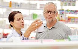 Pharmacist showing drug to senior man at pharmacy Stock Images