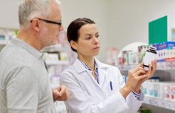 Pharmacist showing drug to senior man at pharmacy Stock Photography