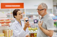 Pharmacist showing drug to senior man at pharmacy Stock Photos