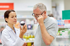 Pharmacist showing drug to senior man at pharmacy Stock Photo