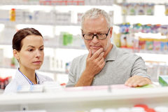 Pharmacist showing drug to senior man at pharmacy Royalty Free Stock Images