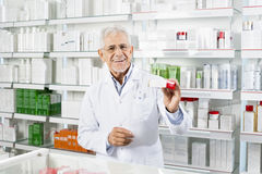 Pharmacist Showing Medicine Box At Counter Stock Images