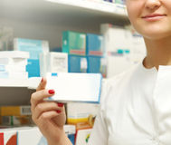 Pharmacist showing medicine box at pharmacy counter Royalty Free Stock Image