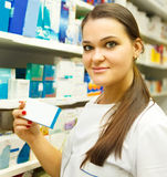 Pharmacist showing medicine box at pharmacy counter Royalty Free Stock Images