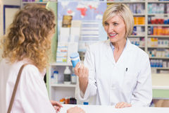 Pharmacist showing medicine jar to costumer Royalty Free Stock Photos