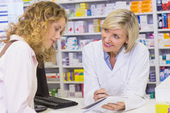 Pharmacist showing prescription to a customer Royalty Free Stock Photography