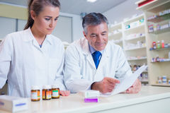 Pharmacist showing a prescription to his trainee Stock Photography