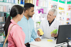 Pharmacist Showing Products To Couple At Checkout Counter. Smiling pharmacist showing products to multiethnic couple at checkout counter in pharmacy stock images