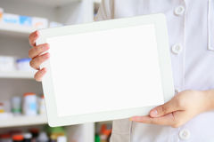 Pharmacist showing tablet computer over pharmacy background. Female pharmacist showing tablet computer over pharmacy drugstore background Royalty Free Stock Photos