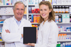 Pharmacist showing tablet pc. At hospital pharmacy Royalty Free Stock Images