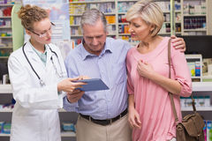 Pharmacist showing tablet pc to costumers. At pharmacy Stock Photo