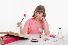 Pharmacist sitting at a table with tweezers on the pill Stock Photo