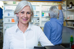 Pharmacist smiling and co-worker checking medicines Stock Photography