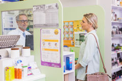 Pharmacist speaking with cheerful young customer Royalty Free Stock Photography