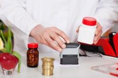 Pharmacist Stamping Bill At Pharmacy Desk Stock Photo