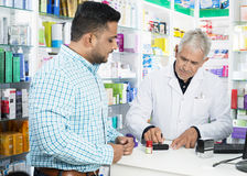 Pharmacist Stamping Paper While Customer Standing At Counter. Senior male pharmacist stamping paper while customer standing at counter in pharmacy Royalty Free Stock Photos