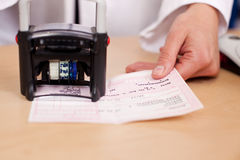 Pharmacist Stamping Prescription At Desk Royalty Free Stock Photo