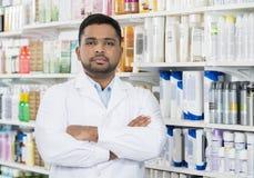 Pharmacist Standing Arms Crossed Against Shelves In Drugstore Stock Photography