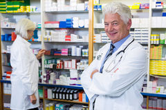 Pharmacist standing with arms crossed and co-worker checking medicines Stock Photos
