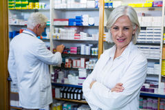 Pharmacist standing with arms crossed and co-worker checking medicines Royalty Free Stock Images