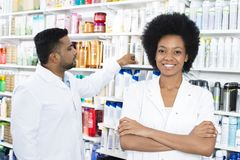 Pharmacist Standing Arms Crossed While Colleague Arranging Produ. Portrait of confident female pharmacist standing arms crossed while colleague arranging royalty free stock photo