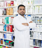 Pharmacist Standing Arms Crossed By Shelves In Drugstore Royalty Free Stock Images
