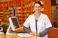 Pharmacist standing at checkout. Happy pharmacist standing at checkout counter in a drugstore royalty free stock photos