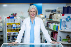 Pharmacist standing at counter in pharmacy. Portrait of pharmacist standing at counter in pharmacy stock photo